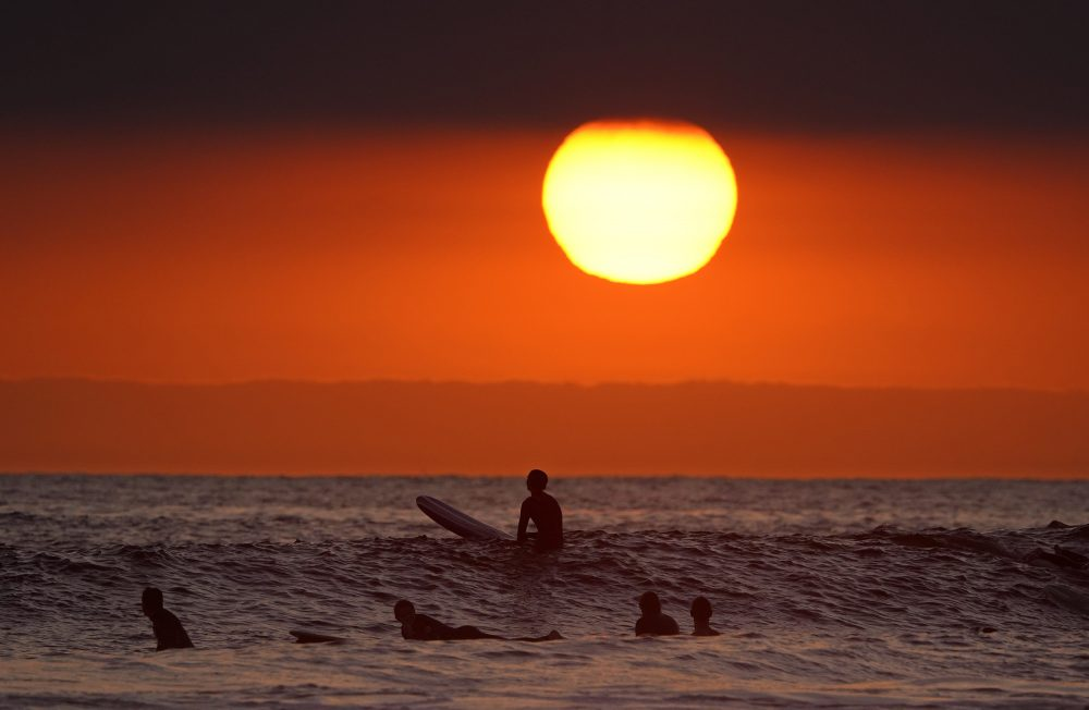 Surfers wait for waves as the sun goes down the day before the beach is scheduled to close during the coronavirus outbreak, Thursday in Newport Beach, Calif. California Gov. Gavin Newsom on Thursday temporarily closed Orange County's coastline after large crowds were seen there.