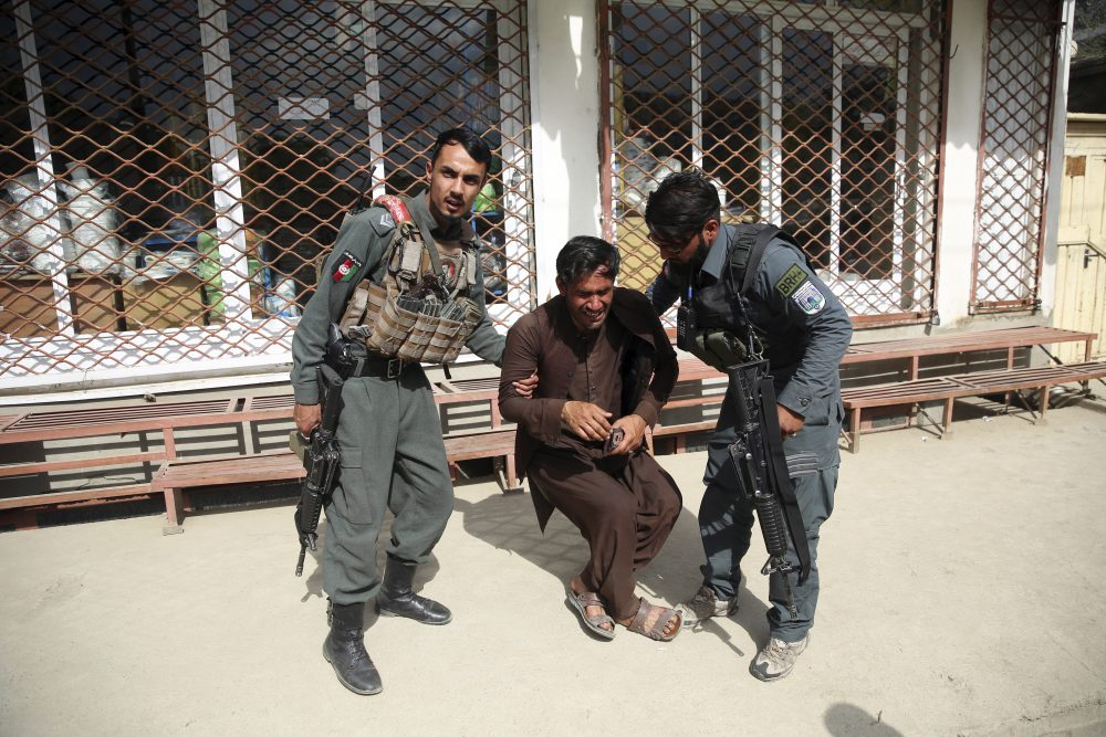 Afghan policemen comfort a man after an attack Tuesday on a maternity hospital in Kabul, Afghanistan. Militants stormed a maternity hospital, setting off an hours-long shootout with the police and killing over a dozen people, including two newborn babies.