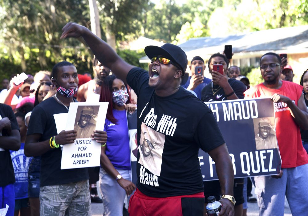 Keith Smith speaks to a crowd Tuesday as they march through a neighborhood in Brunswick, Ga., demanding answers regarding the death of Ahmaud Arbery.