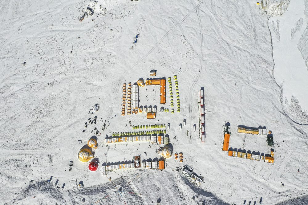 In this April 30, 2020, aerial photo released by China's Xinhua News Agency, vehicles and tents are seen at the base camp at the foot of the peak of Mount Qomolangma, also known as Mount Everest, in southwestern China's Tibet Autonomous Region.