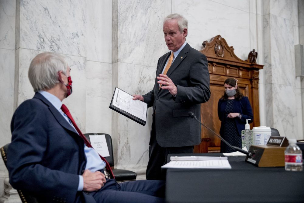 Chairman Sen. Ron Johnson, R-Wis., speaks with Sen. Rob Portman, R-Ohio, left, at the conclusion of a Senate Homeland Security and Governmental Affairs committee meeting on Capitol Hill in Washington on Wednesday after voting to issue a subpoena to Blue Star Strategies.
