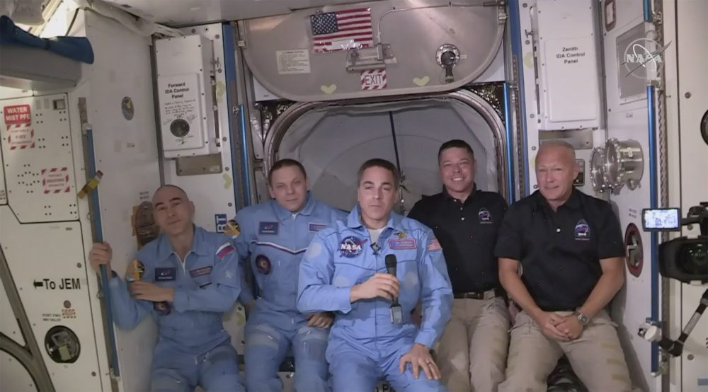 Bob Behnken and Doug Hurley, far right, join the the crew at the International Space Station, after the SpaceX Dragon capsule pulled up to the station and docked Sunday. The Dragon capsule arrived Sunday morning, hours after a historic liftoff from Florida. It's the first time that a privately built and owned spacecraft has delivered a crew to the orbiting lab.