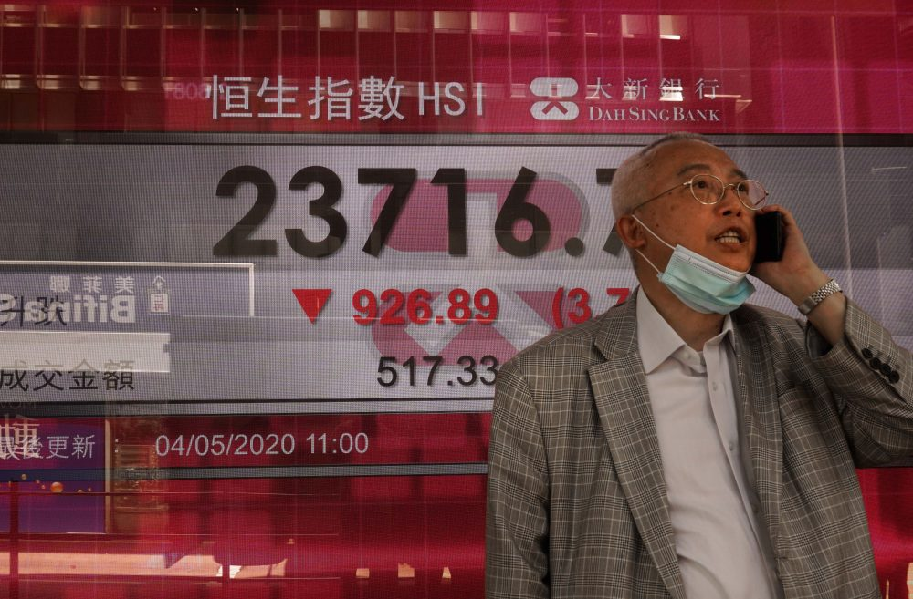 A man wearing a face mask walks past a bank electronic board showing the Hong Kong share index at the Hong Kong Stock Exchange on Monday.