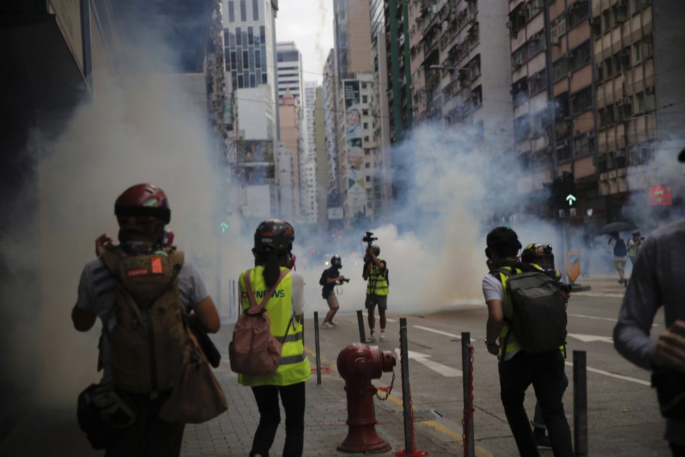 Members of the media take cover as police fire tear gas during a protest against Beijing's national security legislation in Causeway Bay in Hong Kong on Sunday. Hong Kong police fired tear gas in a popular shopping district as hundreds took to the streets to march against China's proposed tough national security legislation for the city.
