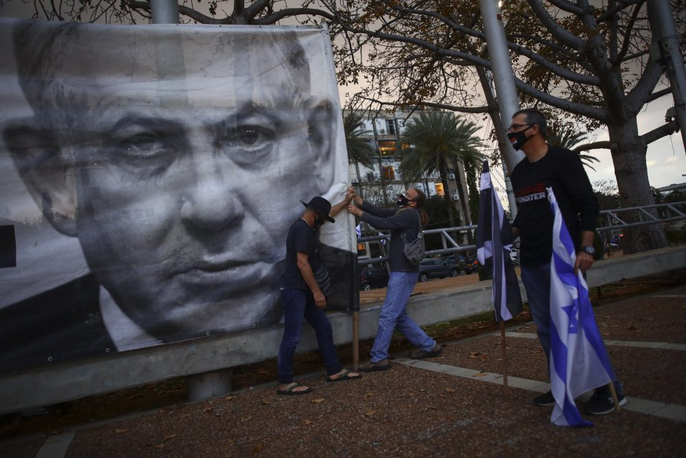 Protesters hang a banner showing Israeli Prime Minister Benjamin Netanyahu on April 25  in Tel Aviv.