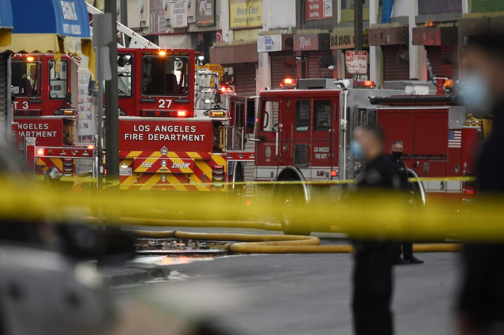 Los Angeles Police Department officers work the scene of a structure fire that injured multiple firefighters, according to a fire department spokesman, Saturday, in Los Angeles.