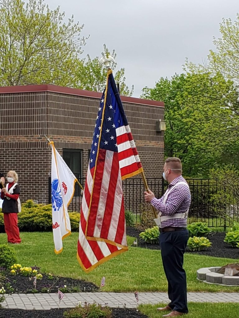 Jake Anderson, administrator at Maine Veterans' Homes — Augusta, participates in the presentation of flags for a Memorial Day Ceremony.