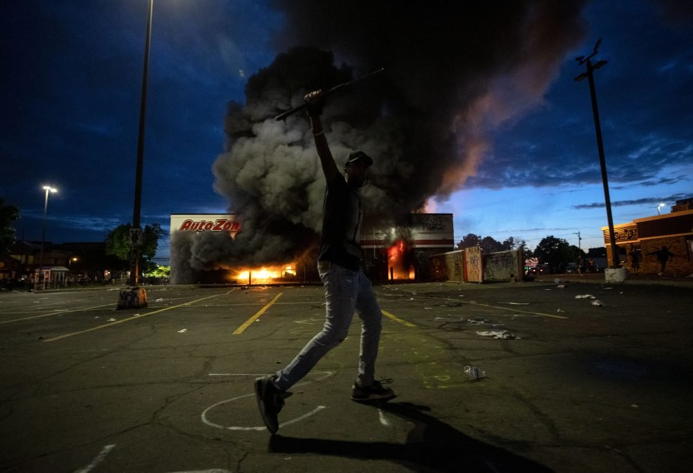 A man poses for a photo in the parking lot of an AutoZone store in flames, while protesters hold a rally for George Floyd in Minneapolis on Wednesday. Violent protests over the death of the black man in police custody broke out in Minneapolis for a second straight night.