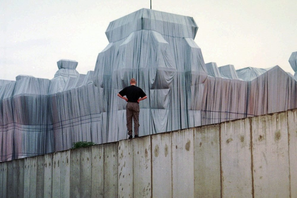 """A man stands at the top of remains of the Berlin Wall and looks at the wrapped Reichstag building, a project titled """"Wrapped Reichstag"""" by American artist Christo and his wife Jeanne-Claude in 1995."""