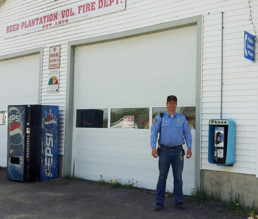 Steve Waite, a fire warden in Reed Plantation, stands by the fire station and the soon-to-be-disconnected public interest payphone. The town wants to replace the payphone, which Waite says he's never seen anyone use, with a vending machine for snacks.
