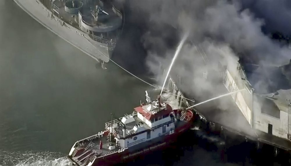 First responders battle a massive fire that erupted at a warehouse early Saturday in San Francisco.
