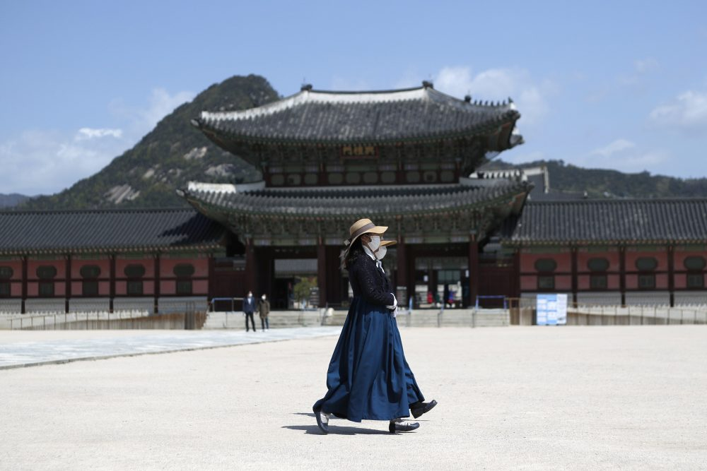 Masked women walk past the Gyeongbok Palace, in Seoul, South Korea. Nervous travelers, spotty air service, health risks –  the battered global tourism industry is facing unprecedented uncertainty in the wake of the new coronavirus.