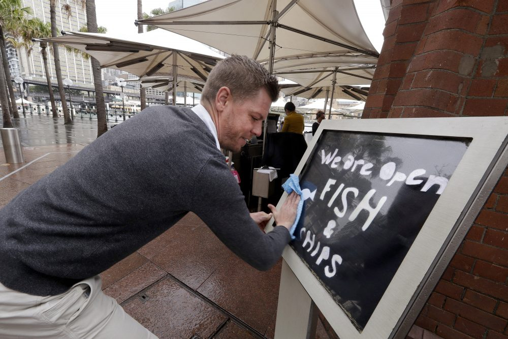 Alec Owes wipes a sign alerting customers that the Sydney Cove Oyster Bar is open as stage 1 of the lifting of COVID-19 restrictions begin in Sydney. Some pubs, clubs and restaurants are reopening with a limit of 10 patrons while following distancing guidelines.