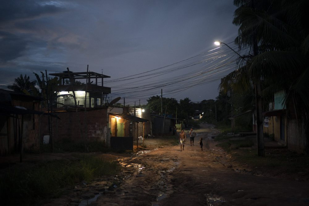 Residents walk on a dirt road in the Park of Indigenous Nations community, in Manaus, Brazil, on May 10. The South American country has Latin America's highest COVID-19 death toll. The country's hardest hit major city per capita is Manaus, where mass graves are filling up with bodies.
