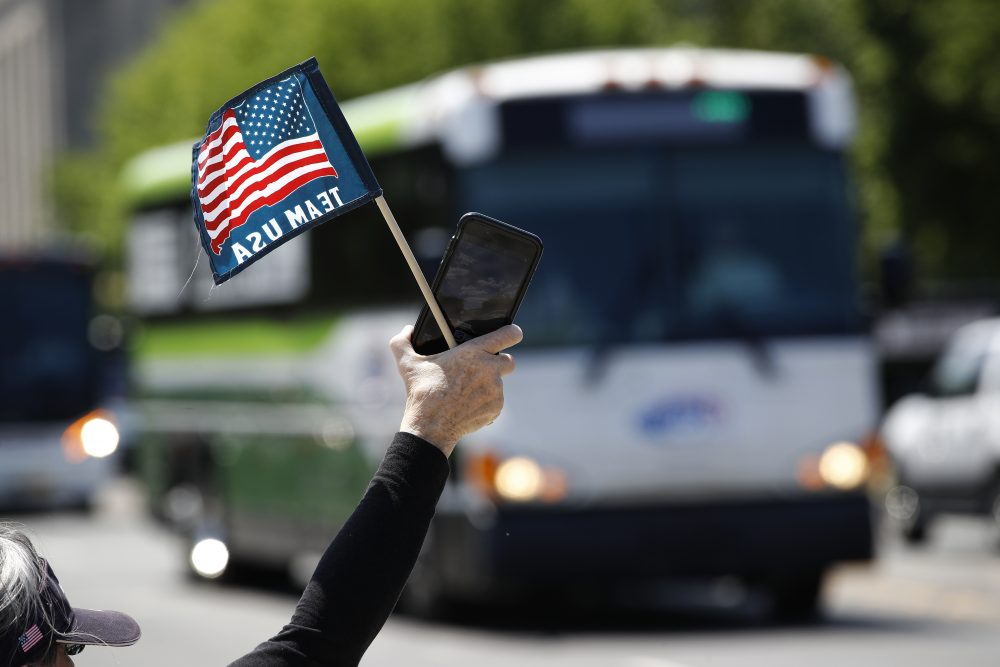 Tour guide Barbara Western waves a flag in support of bus and motor coach operators circling the National Mall in Washington on May 13 for a rally to raise awareness of the industry. America's private buses are ground to a halt, and members of the industry say they need federal assistance to help the country get back to work and play.