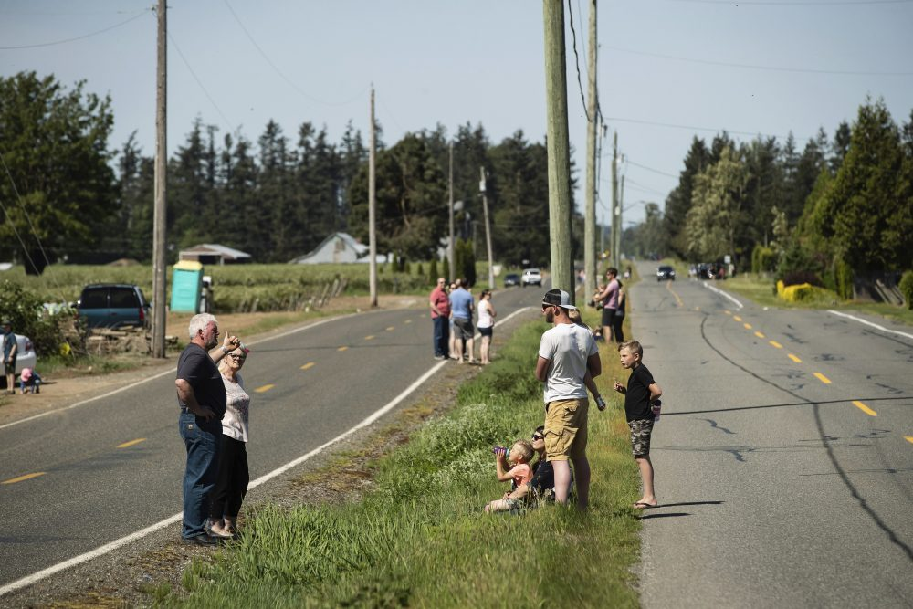 U.S. residents, left, and Canadian residents, right, gather across a ditch along the Canada-U.S. border, in Abbotsford, British Columbia, on May 10. The stretch of international border southeast of Vancouver has become a popular meeting spot for families, loved ones and friends separated due to the closure of the Canada-U.S. border to non-essential travel due to the coronavirus concerns.