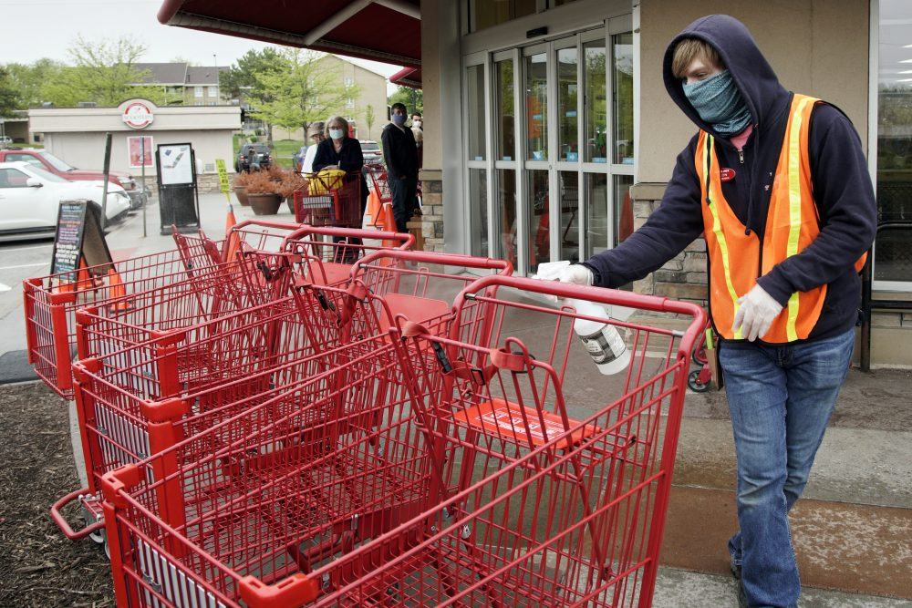 Dilon Moore disinfects shopping carts and controls the number of customers allowed to shop at one time at a Trader Joe's supermarket in Omaha, Neb., on Thursday. Store workers across the country are suddenly being asked to enforce the rules that govern shopping during the coronavirus pandemic.