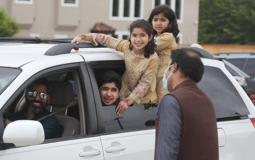 A family looks out from their vehicle during an Eid al-Fitr drive through celebration on Sunday outside a closed mosque in Plano, Texas. Many Muslims in America are navigating balancing religious and social rituals with concerns over the virus as they look for ways to capture the Eid spirit this weekend.