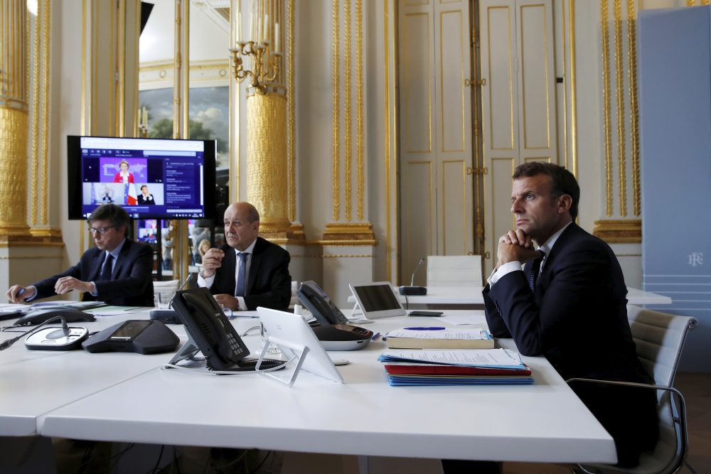 French President Emmanuel Macron listens at the Elysee Palace in Paris as he attends Monday's international videoconference on a COVID-19 vaccine.