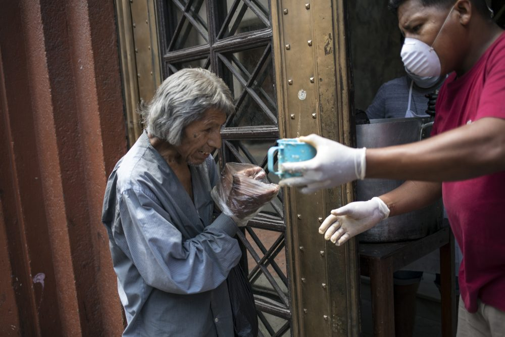 A man uses baggies as makeshift disposable gloves as he reaches for a free cup of soup, in Lima, Peru, on March 26. The coronavirus is raging in Peru, particularly Lima, with 155,671 cases.
