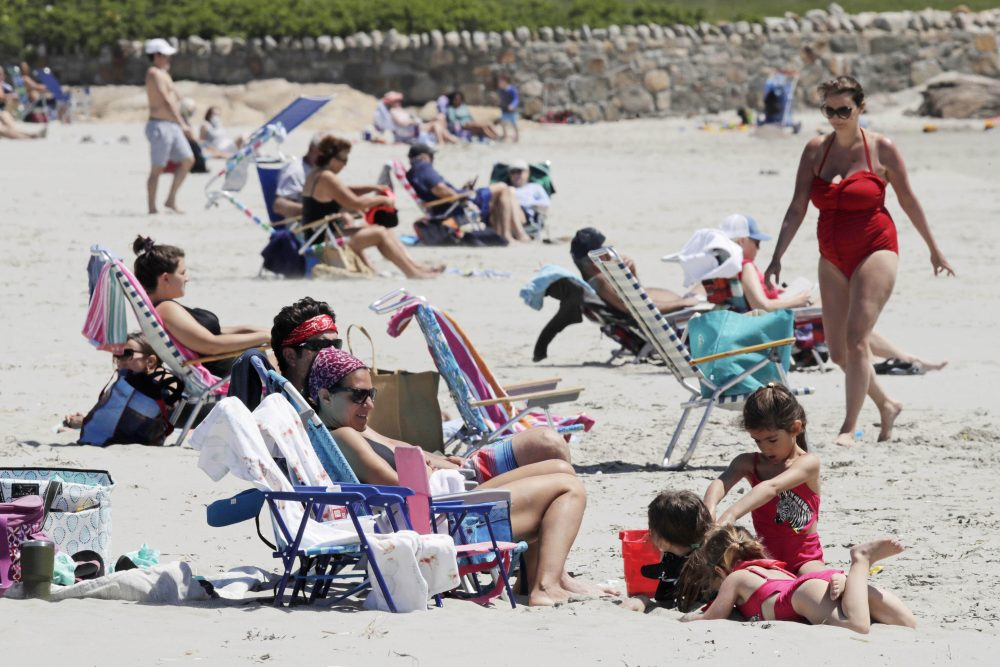 People relax on the shore at Good Harbor Beach in Gloucester, Mass., on Friday. Beaches in Gloucester reopened with restrictions Friday after being closed two months ago because of the pandemic.