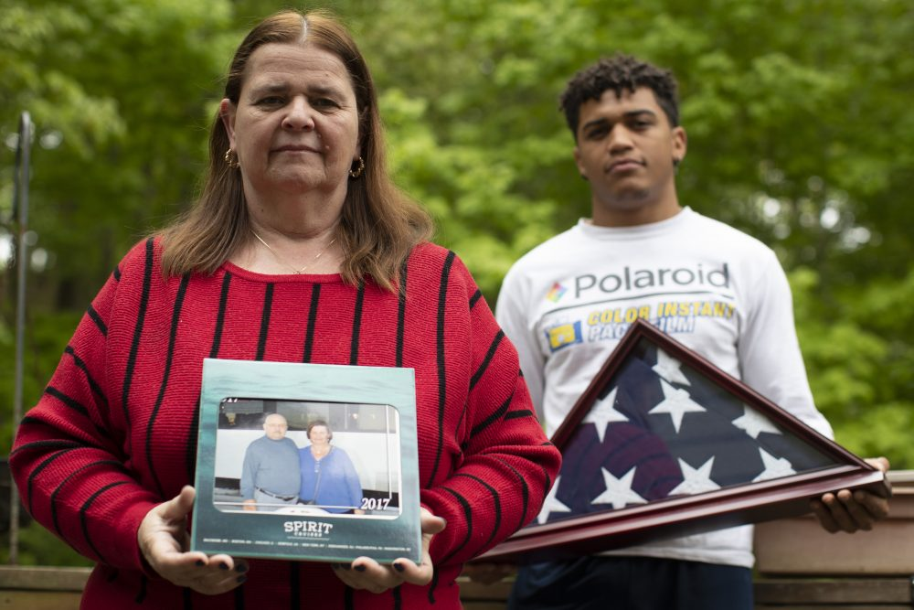 Florence Hopp, left, holds a photograph of herself and her husband Robert Hopp during a cruise in 2017, as her son J.J. Brania-Hopp holds the American flag the military presented to them after his father's death at their home in Boonton, N.J. Robert Hopp was one of at least 79 residents of a veterans home in Paramus, N.J., to die from COVID-19.