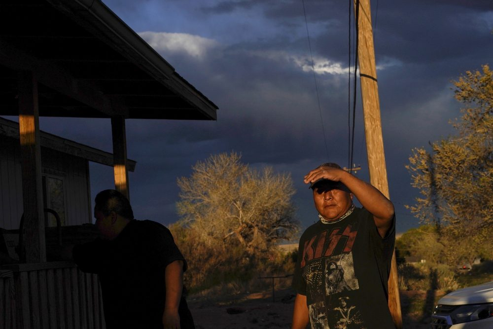 Eugene Dinehdeal shields his face from the setting sun on the Dinehdeal family compound in Tuba City, Ariz., on the Navajo reservation on April 20, 2020. The Navajo reservation has some of the highest rates of coronavirus in the country. If Navajos are susceptible to the virus' spread in part because they are so closely knit, that's also how many believe they will beat it.