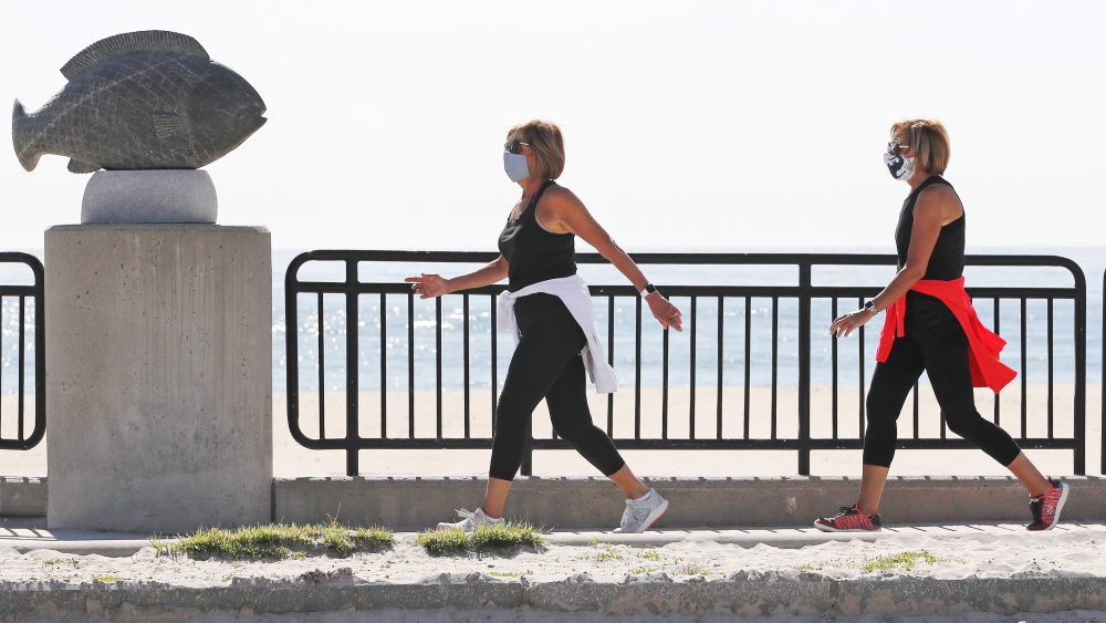 Two women, wearing protective masks due to the COVID-19 virus outbreak, walk on a sidewalk adjacent to an empty Hampton Beach in Hampton, N.H., on Thursday. Beaches in New Hampshire will reopen to swimmers, walkers and runners June 1, but sunbathers will have to wait.