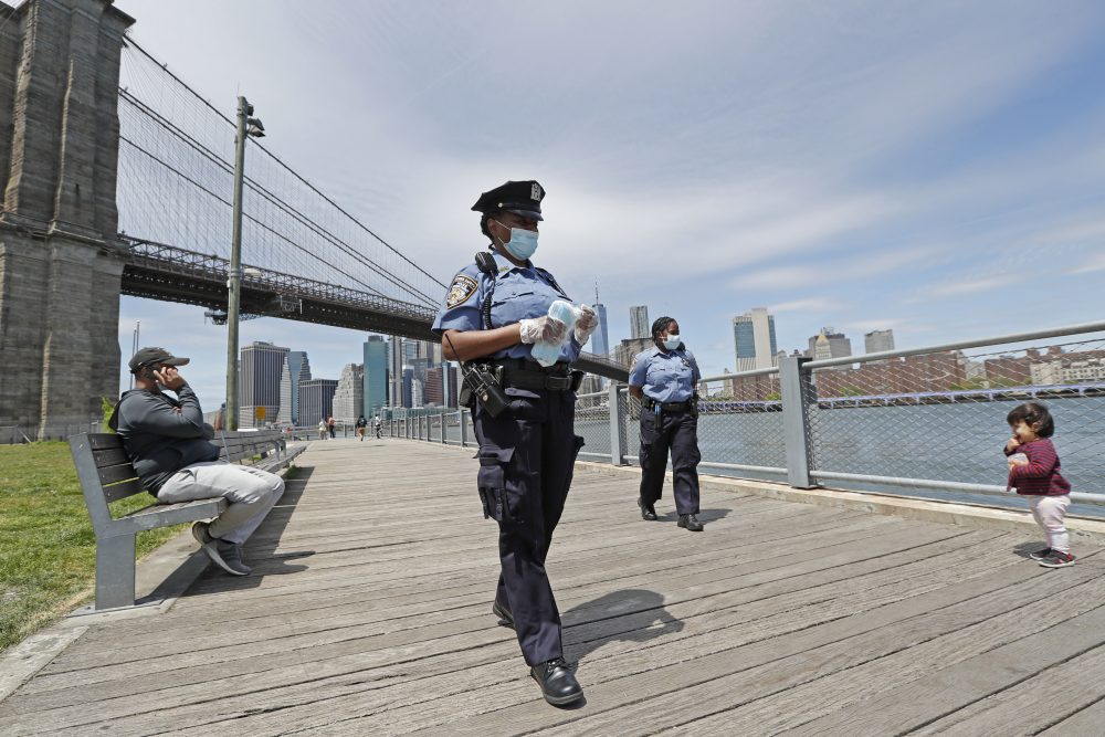 New York City police officers patrol Brooklyn Bridge Park on Sunday and distribute face masks to anyone who needs or asks for one.