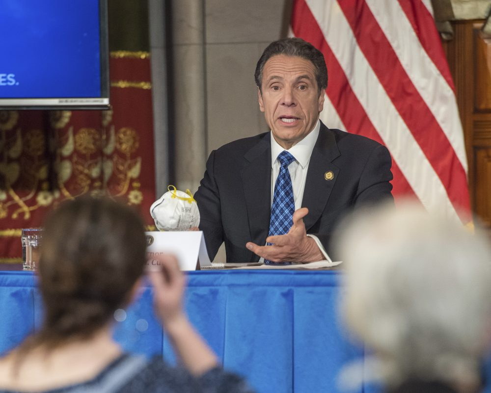 Gov. Andrew Cuomo addresses the media while holding an n95 mask during his daily press briefing on COVID-19 last month in Albany.