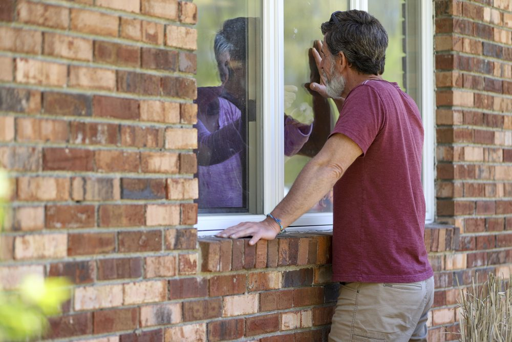 Jack Campise talks with his mother, Beverly Kearns, through her apartment window at the Kimberly Hall North nursing home on Thursday in Windsor, Conn. Nursing home operators say the lack of testing kits and other resources have left them nearly powerless to stop the virus from entering their facilities.