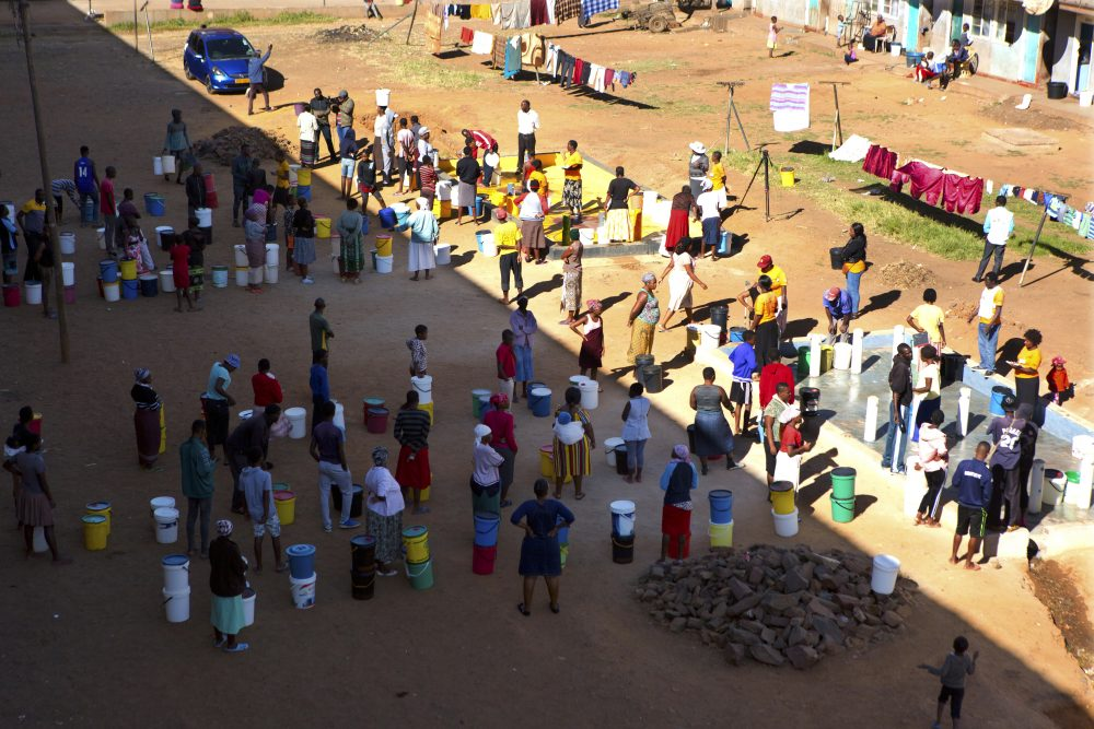 People wait to fetch water April 24 from a row of communal taps that Doctors Without Borders provided in a suburb of Harare, Zimbabwe. In Zimbabwe, clean water is often saved for doing dishes and flushing toilets.