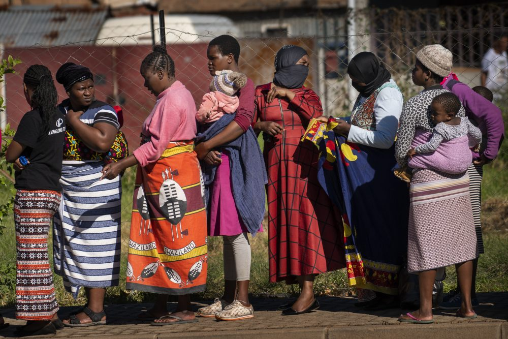 Women carrying their children line up for vegetables from the Jan Hofmeyer community services April 30 in Johannesburg, South Africa. The country is struggling to balance its fight against the coronavirus with its dire need to resume economic activity. The country with the Africa's most developed economy also has its highest number of infections – more than 19,000.