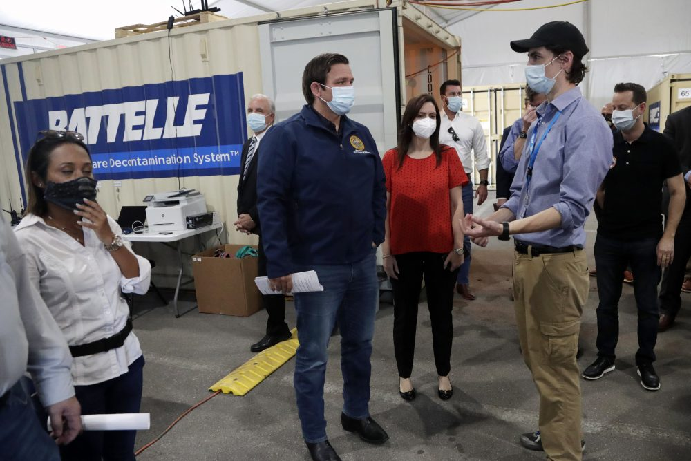 Florida Gov. Ron DeSantis, center, tours decontamination units at a COVID-19 testing site with Sean Harrington of Battelle Critical Care Decontamination System, right, at Hard Rock Stadium on Wednesday in Miami Gardens.