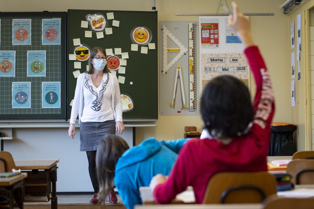 A teacher wears a face mask as she teaches Monday at a primary school in Morges, Switzerland. Swiss primary and secondary schools reopened with half of the students.