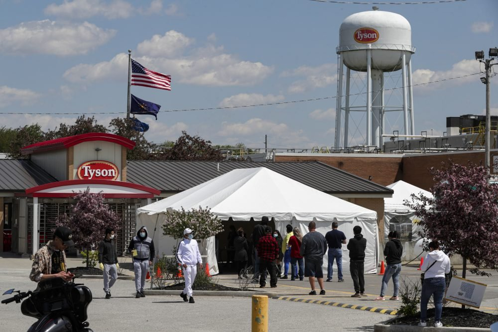 Workers line up to enter the Tyson Foods pork processing plant in Logansport, Ind., on Thursday. In Cass County, home to the Tyson plant, confirmed coronavirus cases have surpassed 1,500. That's given the county, home to about 38,000 residents, one of the nation's highest per-capita infection rates.
