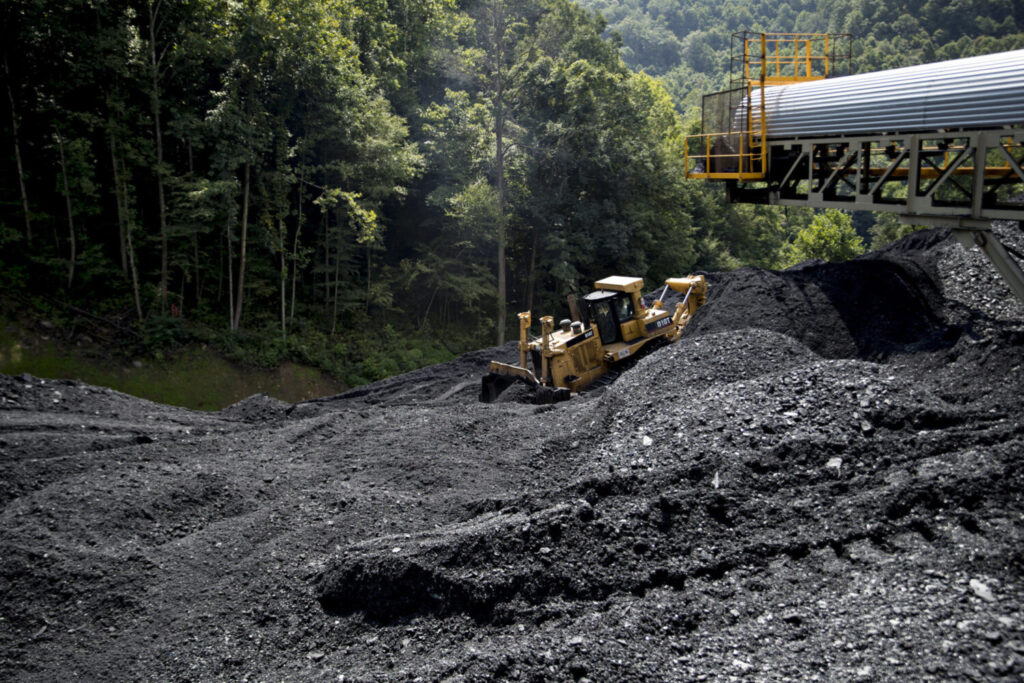 A bulldozer pushes raw coal in West Virginia. Approved PPP loans covered more than 78 percent of the industry's eligible payroll, compared to an average for all industries of 52 percent.