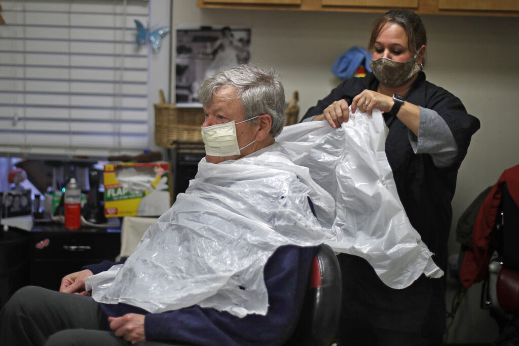 Ann Fouquette uses a trash bag for an apron before cutting Jan Smith's hair at Kilroy's Haircutters on May 1 in Brunswick.