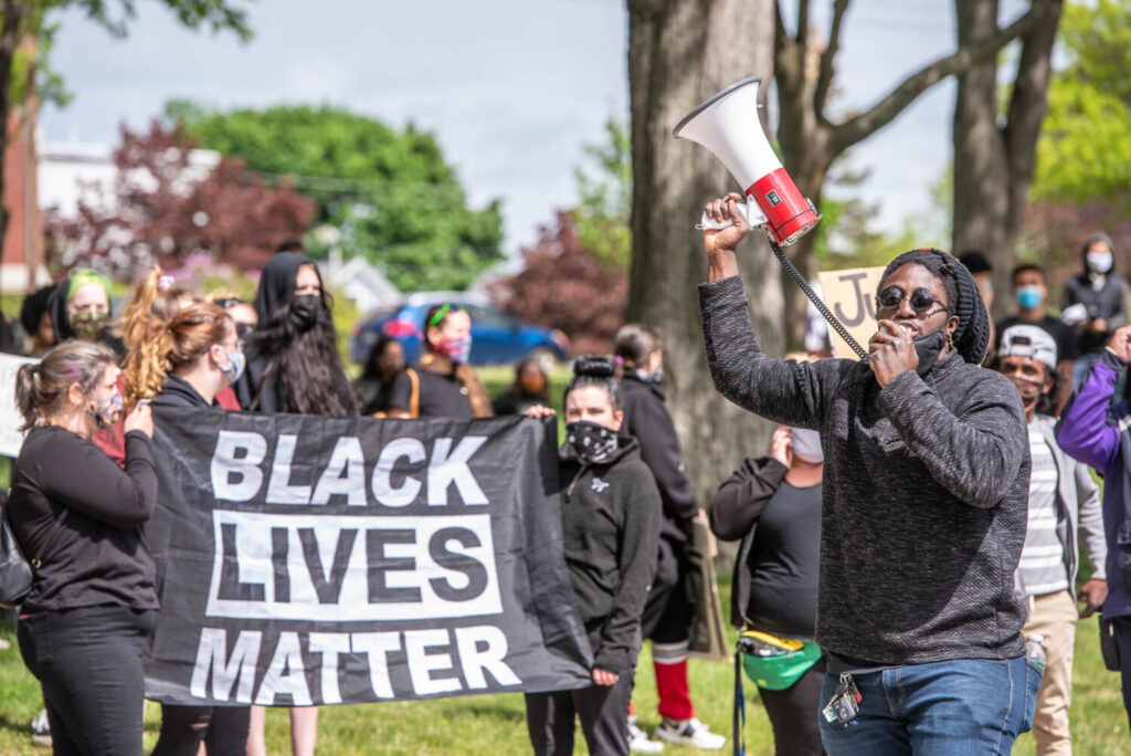Dane Morgan speaks through a megaphone while others hold a Black Lives Matter sign during a rally on June 1, 2020, in Kennedy Park in Lewiston.