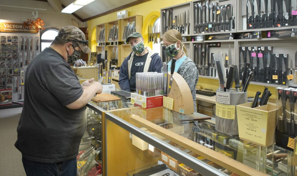 James Conner, left, looks over a knife while talking with Doug Dillman, center, and Jason Dillman of Casco Bay Cutlery & Kitchenware in Freeport on Monday, the first day nonessential retail businesses could open in southern Maine.
