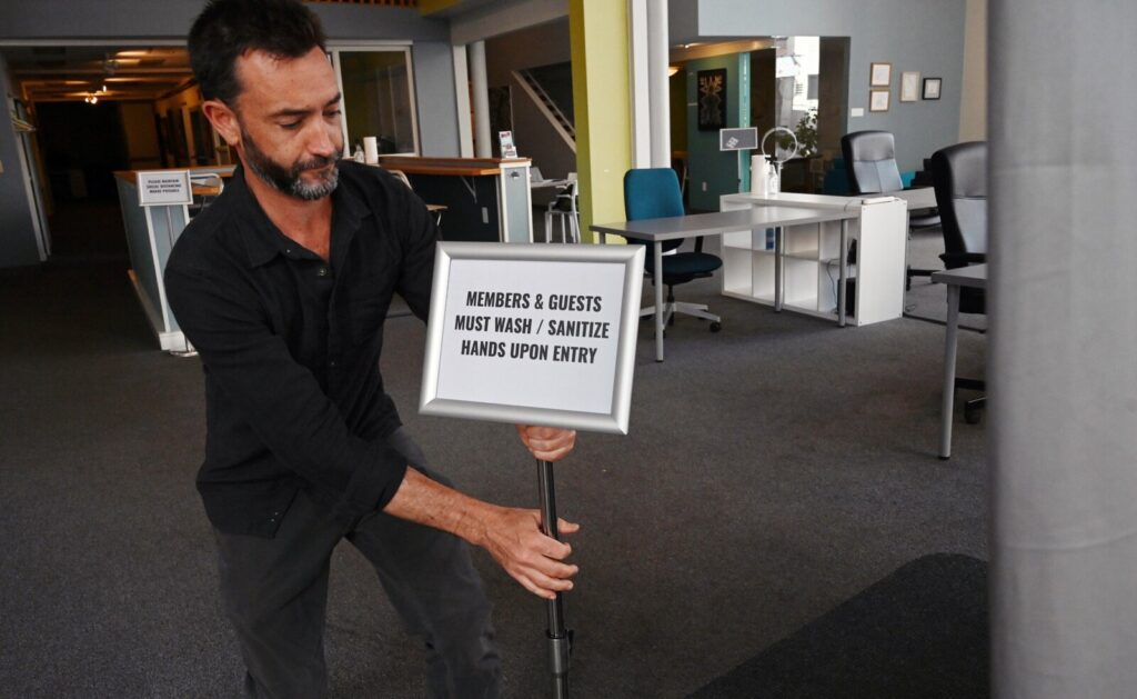 Patrick Roche of Think Tank Coworking puts a sign near the entrance to remind members and guests to sanitize hands Thursday in Portland. Startup companies, and businesses that cater to them such as Think Tank, have undergone dramatic changes because of the pandemic.