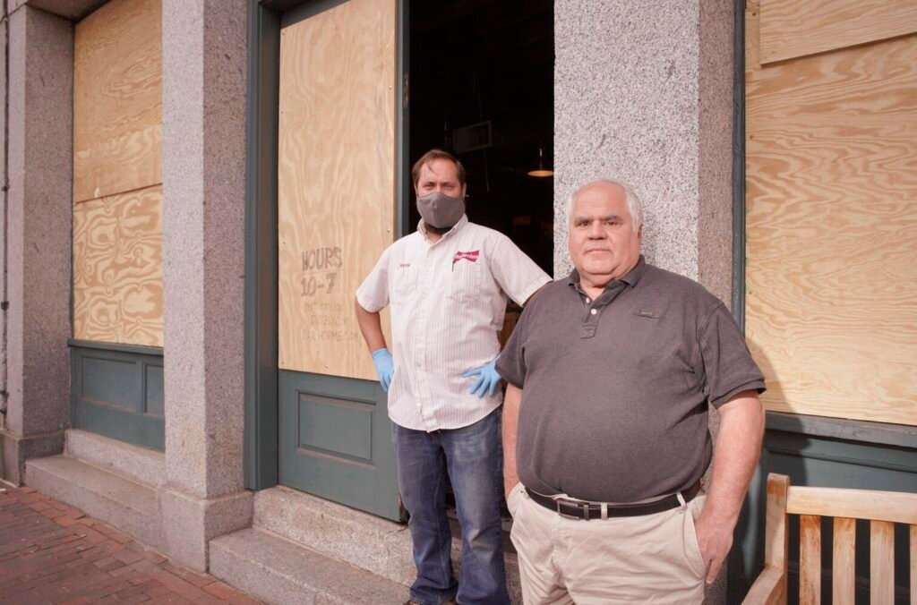 Owner Jacques deVIllier, right, and manager Kevin Casey stand in front of the boarded-up windows of Old Port Spirits and Cigars on Commercial Street in Portland on Thursday. The windows were broken Monday night by looters who stole beer and liquor from the store.