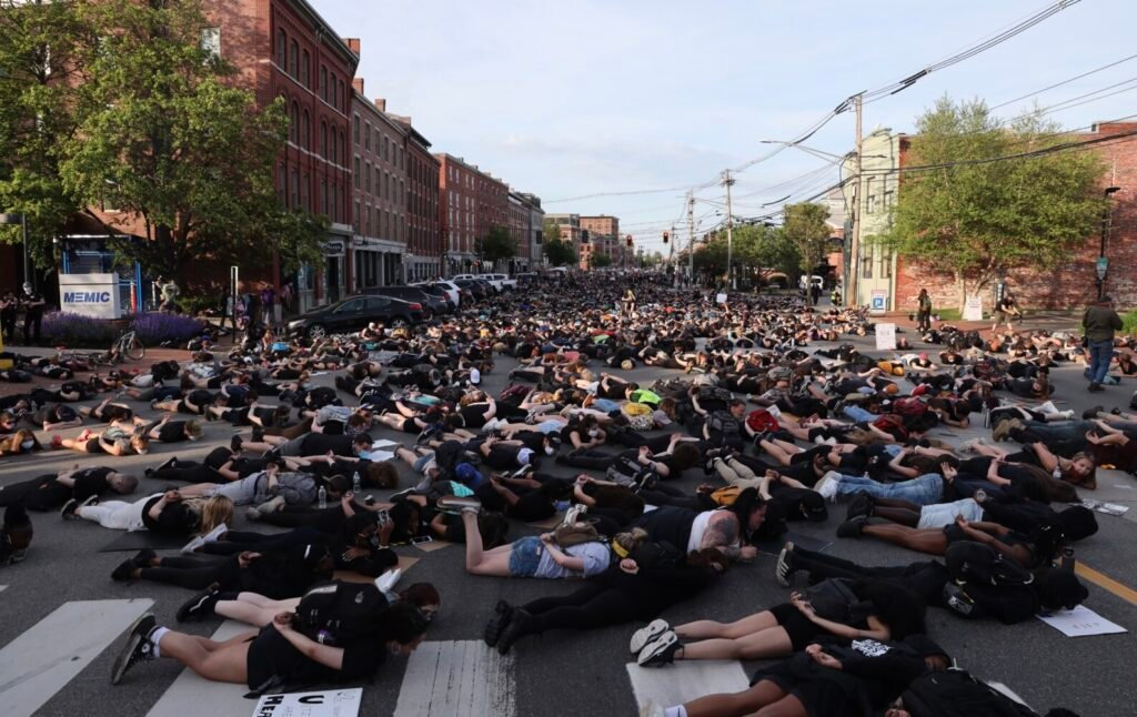 Protesters stop marching to lie on the ground on Commercial Street during a massive demonstration Friday night.