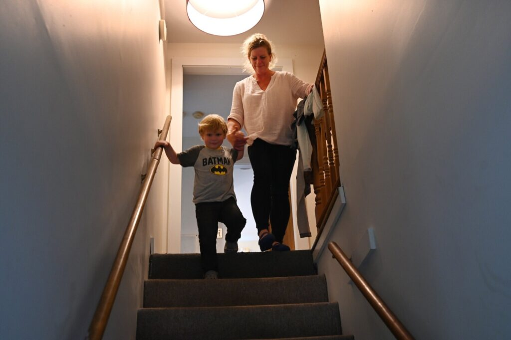 Rebecca Giles and her four-year-old son Andrew Benner make their way down the stairs of their apartment on June 11. Giles lost her housing and income because of the coronavirus pandemic and was living in a hotel recently until she was able to find an affordable apartment.
