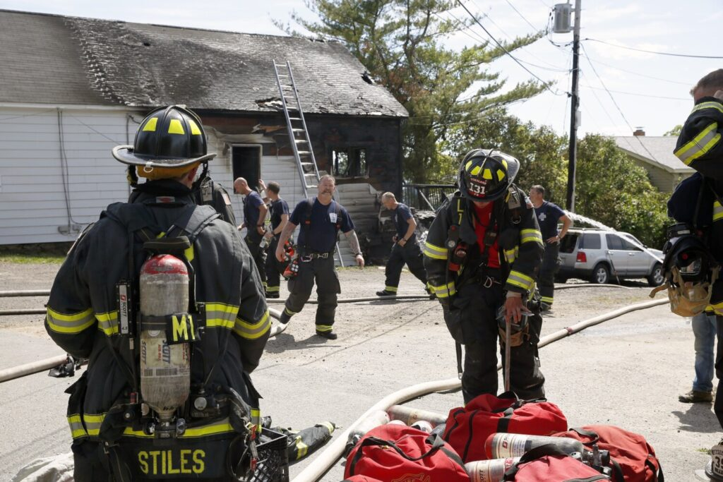 Firefighters work at the scene of the fire at the Peaks Island post office on Monday.