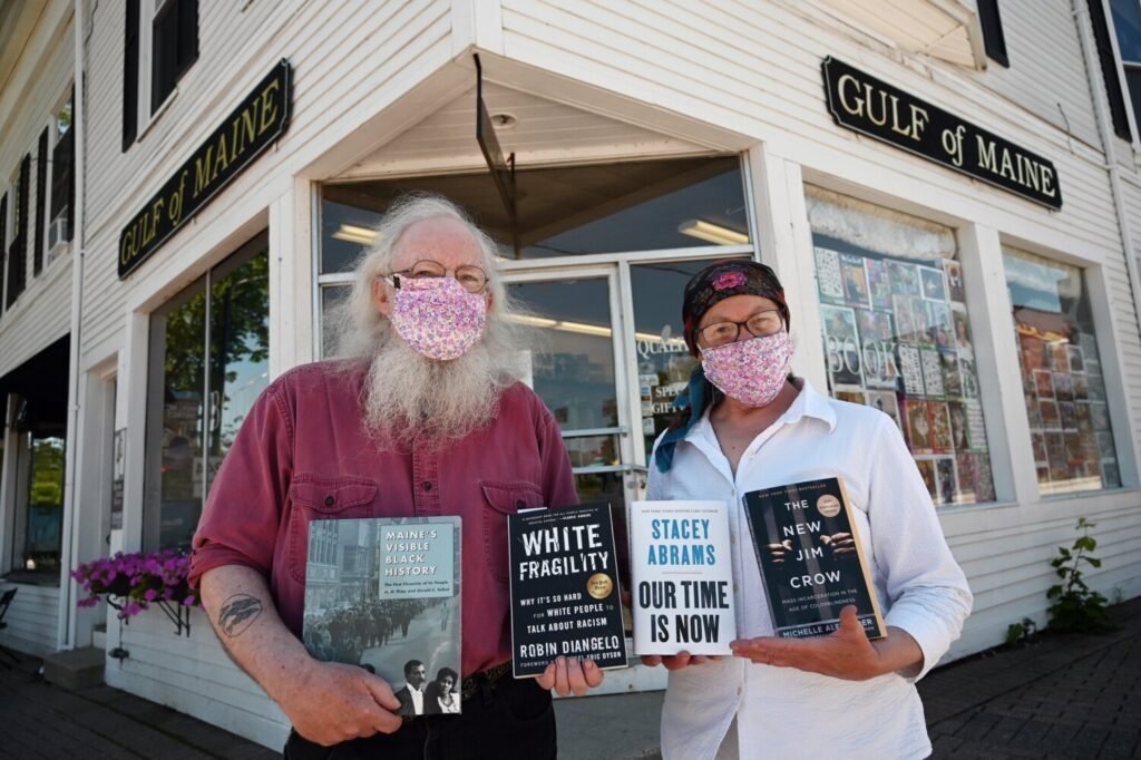 Gary Lawless and Beth Leonard, co-owners of Gulf of Maine Books in Brunswick hold books on race outside their book store. Books about race are in high demand at libraries and book stores in Maine, in response to the Black Lives Matter protests.