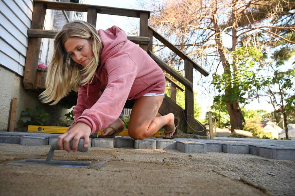 Susie Graham of Cape Elizabeth levels the sand while helping to build a backyard patio with her family last week. While the coronavirus outbreak has hampered other sectors of the economy, business is booming for retailers that cater to home improvement projects.