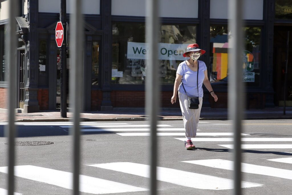 A woman crosses the intersection of Middle and Exchange streets in Portland on Wednesday. Several blocks of Exchange Street have been closed off for pedestrian traffic and outdoor dining.