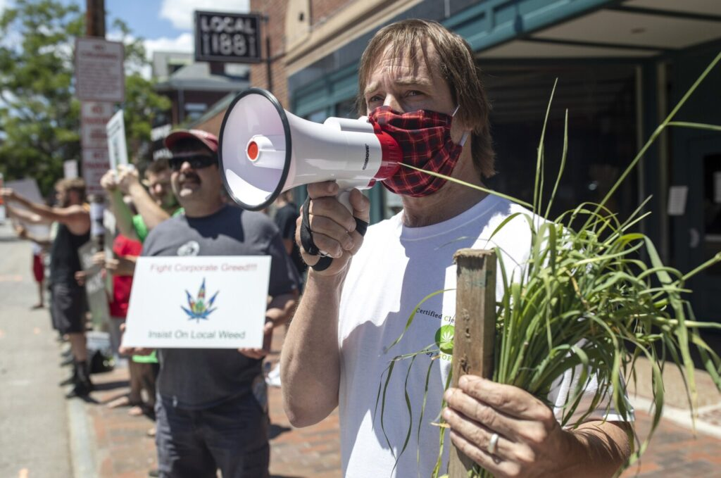 Dawson Julia, the director of the Maine Cannabis Coalition, leads a protest outside of Wellness Connection's store in Portland on Friday. The group was protesting the company's legal efforts to push the city of Portland and Maine to allow out-of-staters to have equal access to the recreational marijuana industry.