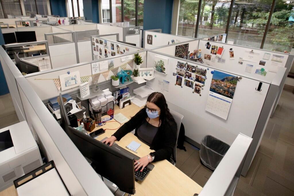Rachel Eggleston, a claims associate at MEMIC in Portland, is one of two people who are working on her floor. MEMIC is among the businesses whose employees are slowly returning to the office, practicing social distancing, wearing masks and sanitizing surfaces.